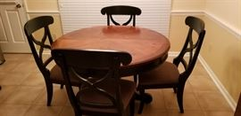Wood finish kitchen table with 4 upholstered seat black chairs