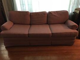 three-seater rose colored fabric sofa
