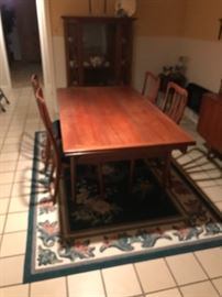 MCM Expandable Dining room table with 4 chairs and matching sideboard. Area rug is also for sale. In the background is a nice antique china cabinet!