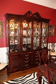 Stately four door breakfront with lighted shelving above and door and drawer storage below by Thomasville