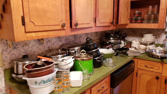 a kitchen full of pyrex, pots and pans, corning ware, and fire king