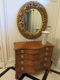 Large round carved frame beveled mirror and a serpentine dresser by Winterthur.