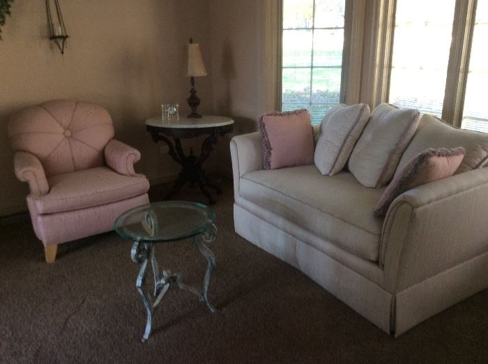 Pink chair and white sofa round glass and metal side table. Marble and wood side table.