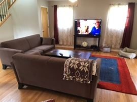 2 more sofas and one of many flat screen TVs