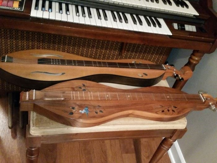 The nearest dulcimer is the beautifully made 'Smoky River' model by Walnut Valley Dulcimer.   The other dulcimer has no name brand but the model number is DC-200.