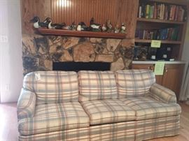 Multi color pastel couch,  Duck decoys, collectibles and books series such as The Old West by Time Life Books