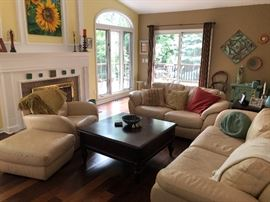 Leather couches and chair with ottoman; hard wood coffee table.