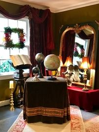 A corner of the LR  Velvet tablecloth with a collection on globes an antique  podium with Victorian plaster mirror with gilded trim and a bronze putti