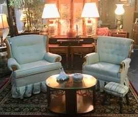 Two nicely upholstered pale green swivel rockers with a small plaid footstool
