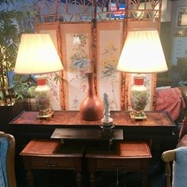 Black sofa table with a pull-out shelf, two wooden end tables with drawers, and two matching oriental lamps