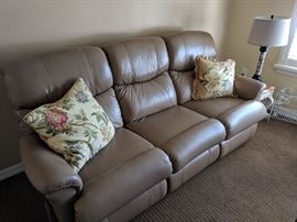 Tan leather sofa with recliners on both ends. Sofa is in like-new condition