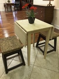 This is a very cute little drop leaf table. Also 3 wood stools with Rattan swivel seats.