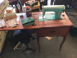 White sewing machine in cabinet with sewing accessories