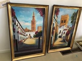 """Painting set / Item(s) Description 2 @ 26""""x17"""", village scene set with gold frames signed from Spain  How Many in Lot 2  Signed X  Number of Photo 8  Location Dining Room"""