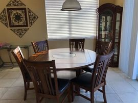 Round dining table with 6 chairs $600. Cabinet behind table for $200.