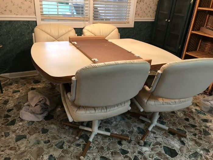 #32White Laminate Table w/1 leaf and 4 rolling Pleather Chairs   53-70x35x29.5 $75.00