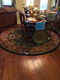 table with 4 leather chairs and 8 foot round rug