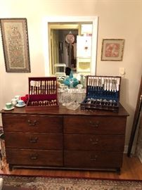 Godinger & Wallace Silverware Sets on an antique chest of drawers.
