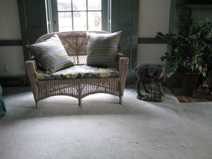 Wicker settee with Plow and Hearth cushions.                                     With cute moose table.