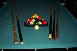 Cues, rack and balls included with pool table