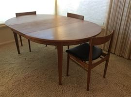 "Mid-century Danish teak dining table - 48"" round. Has three 20"" leaves (one leaf in place in photo) Extends to 9 ft. long with all leaves in place.  Purchased new in 1965."