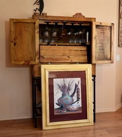 Southwest art and unique bar that has a drop down shelf when in use along with a wine rack at the bottom and places to hang your glasses.