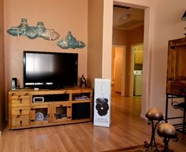 TV for sale and entertainment center along with more famous artist's work.