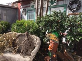 In front of the Warehouse, a wicker love seat, metal garden and seasonal garden art