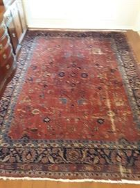 Isparta area rug. Wool on cotton with a Persian pattern. 80+ years old, well used.  Fair condition. 9'x12' pile carpet. Rose and blue colors make this a very unique piece