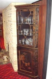 Oriental style black lacquer and decorated corner cupboard.