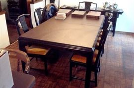 Oriental style dining table with eight chairs and two extension leaves.