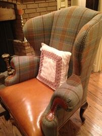 One of two handsome leather and plaid upholstered chairs