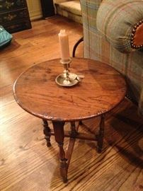 Round antique English oak table; brass candle holder