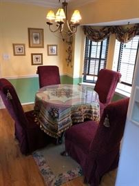 Glass top kitchen table with upholstered dining chairs.