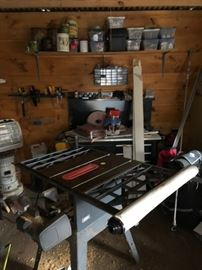 Saw table, saws, chainsaws, boxes of hardware and tools.