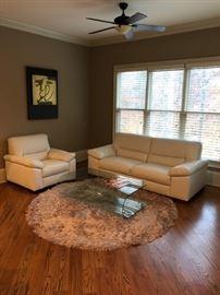 Natuzzi Italian leather sofa and chair.  Modern, glass coffee table and circular rug.