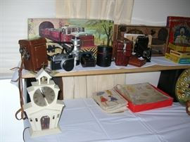 """Vintage cameras, an Atlas boxed N-gauge train set, MasterCrafters church clock (it works!), some vintage patterns and wrapping paper. In that blank spac e? Tons of our patented costume jewelry """"Bags O' Fun"""". Happy hunting!"""