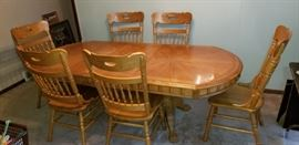 Beautiful Oak Dining Table with leaf inserted and 6 like new heavy pressed back chairs.