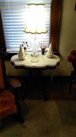 Small white ceramic Christmas trees on marble top table with Waterford lamp