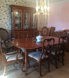 Lovely dining room table and six chairs! Gorgeous wood. Also pictured, a beautiful china cabinet and two different chairs. One looks Victorian-like and the other is carved wood with a leather-looks seat.