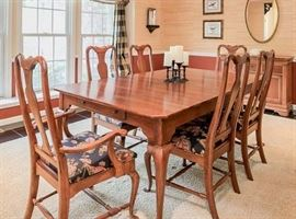 Graceful Queen Anne design dining room table with eight-chairs, two of which are captains chairs.
