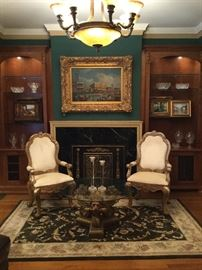 Plunkett velvet wood arm chairs (24w x 21.5 d x 44h); Original oil artwork with custom gilt gold frame (artwork with frame 38h x 48w); antique metal fireplace screen (32h x 41w); wool area rug (5 x 8); lion's head gold pedestal with glass table top (36diameter x 20h)