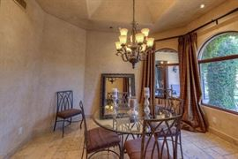 Breakfast nook glass top table  hanging mirror and draperies and glass chandelier with swag arms
