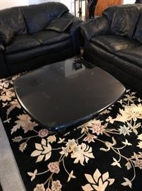 Black leather type sofa, love seat and matching chair with ottoman, black coffee table and 2 side tables with matching Black lamps with cocoa shades, black and floral rugs