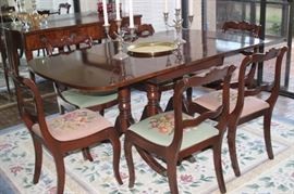 Duncan Phyfe style dining table with leaves and pads and needlepoint chairs.