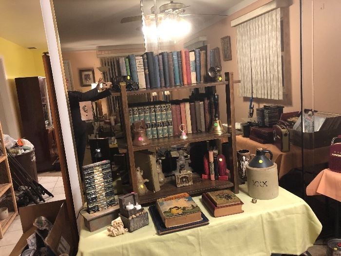 Waterfalls, metal car bank, bells, book ends, antique books, oil lamp fireplace figure, and antique headlamp light.