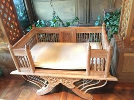 One of two carved wood gallery chairs with cushions.