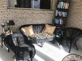 A sunporch filled with black wicker furniture