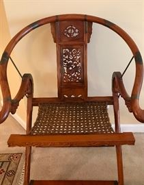 One of my favorite pieces in the sale. This is a gorgeous folding Chinese Emperor Hunting  chair (set of 2) that was purchased in Singapore by the owner in 2000. The reproduction Huanghauli wood and horseshoe back with brass accents is beautiful. The chairs have sisal webbing seats. The care and talent put into the chair carvings shows nothing but perfection. The chair is comfortable and light weight.