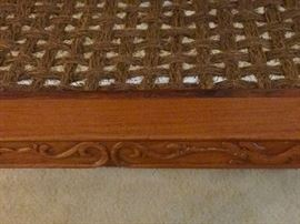 The sisal webbing seat with an intricate design on the front.